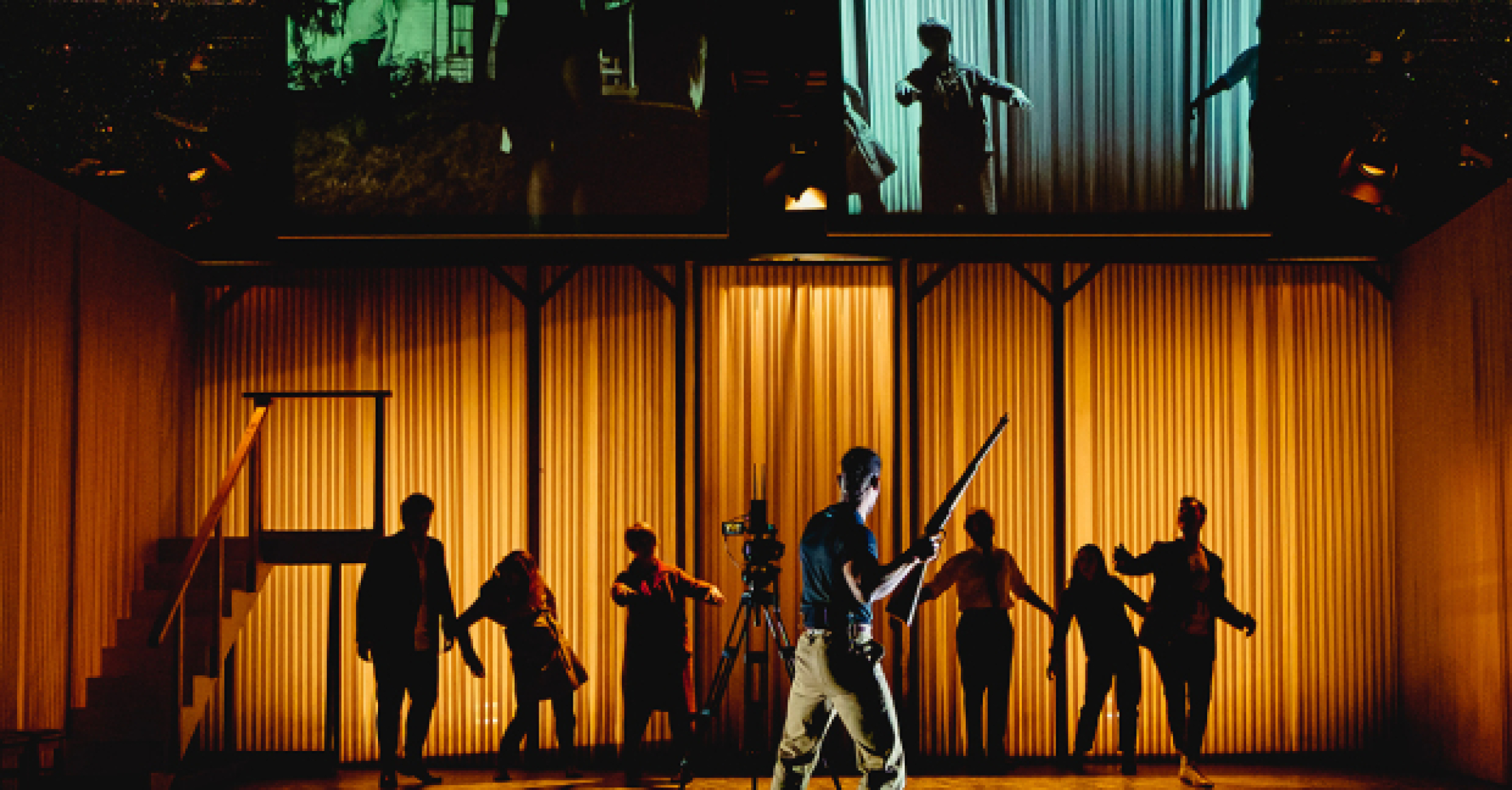 On a stage, a man holds up a gun towards a group of silhouetted zombies, while screens above show a film and a live feed.